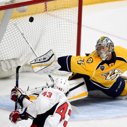 Nashville Predators center Cody Bass (16) shoots wide of the net past Washington Capitals defenseman Dmitry Orlov (9), goalie Braden Holtby (70), and defenseman Taylor Chorney (4) during the first period at Bridgestone Arena, Tuesday, Feb. 9, 2016, in Nashville, Tenn.