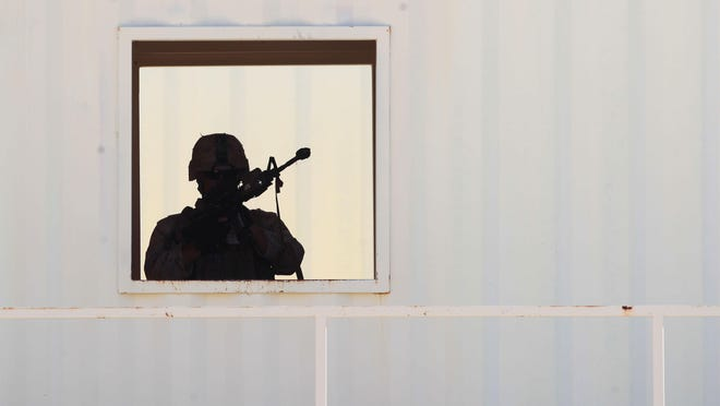 Marines of Fox Company, 2nd Battalion, 1st Marine Regiment, 13th Marine Expeditionary Unit Battalion Landing Team conduct urban warfare training on Range 215 at Marine Corps Air Ground Combat Center, Twentynine Palms on Tuesday, Sept. 1, 2015. In this photo a soldier is seen through a window as they enter a building.