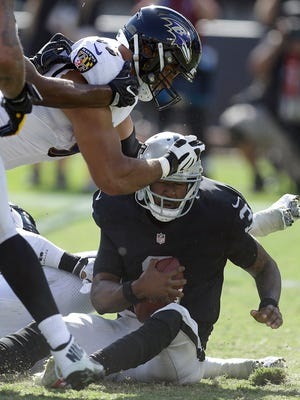 Oakland Raiders quarterback EJ Manuel, right, is sacked by Baltimore Ravens outside linebacker Terrell Suggs, bottom rear, during the second half of an NFL football game in Oakland, Calif., Sunday, Oct. 8, 2017. (AP Photo/Ben Margot)