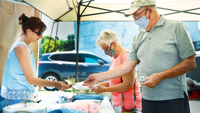 Karol Thewlis, left, checks out Nancy and Ron Boyd during the Lincoln Highway Buy-Way Yard Sale on Thursday. Thewlis' best friend, Valerie Hall, has a seven-family sale on her property at County Roads 30A and 175 in Jeromesville.