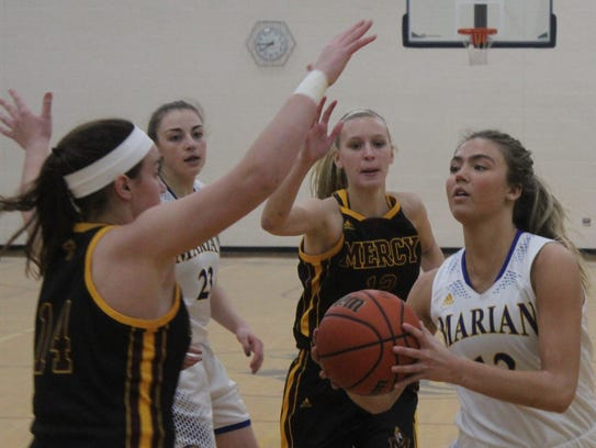 Marian junior Olivia Moore (12) drives to the net past