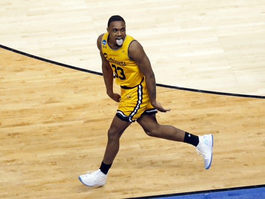 UMBC's Arkel Lamar reacts after making a basket against Virginia during the second half of a first-round game in the NCAA men's college basketball tournament in Charlotte, N.C., Friday, March 16, 2018. (AP Photo/Chuck Burton)