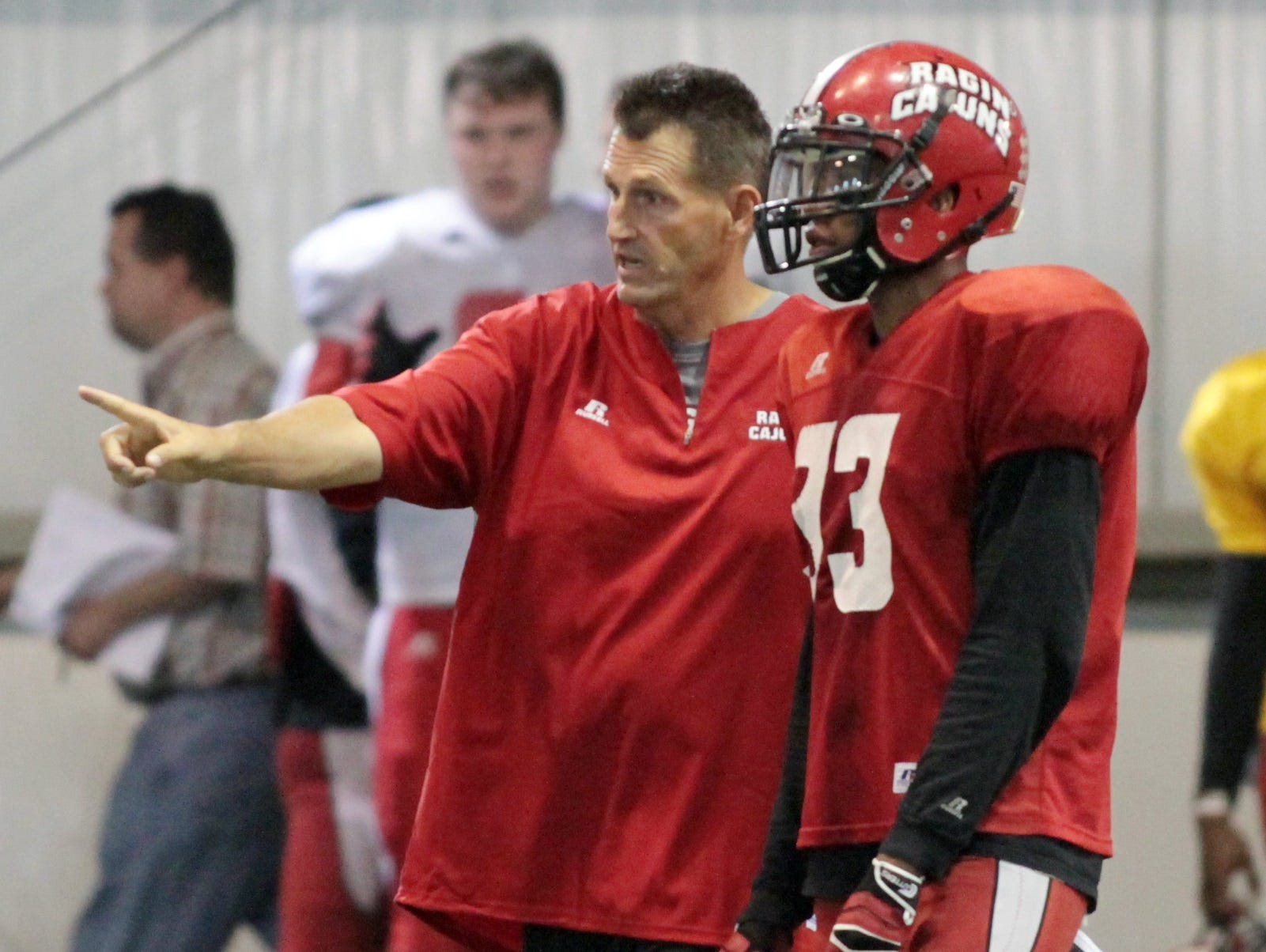 UL assistant coach David Saunders, shown here giving instruction to UL defensive back Trevence Patt (33) last season, has left the Ragin' Cajuns coaching staff 'for personal reasons.' UL safety Trevence Patt (33) gets instruction from cornerbacks coach David Saunders during practice.