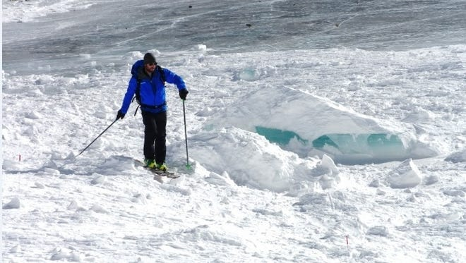 An avalanche expert surveys the scene of a deadly avalanche earlier this month near St. Mary's Lake, Colo.