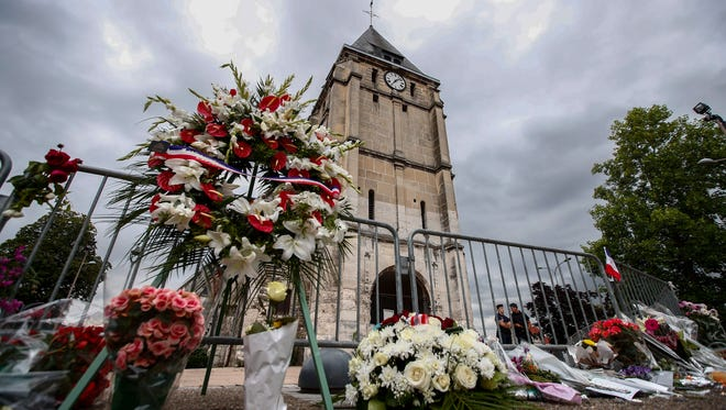 People pay tribute at a makeshift memorial near the Saint Etienne church, where priest Jacques Hamel was killed, in Saint-Etienne-du-Rouvray, near Rouen, France.