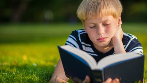 boy reading a book in the park
