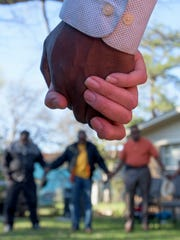 Members of the community hold hands and pray as they hold a vigil, on Saturday February 25, 2017, for Greg Gunn one year after he was shot and killed, by Montgomery police officer Aaron Cody Smith, in front of his home on McElvy Street in Montgomery, Ala.