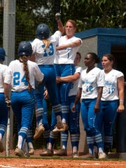 University of West Florida's Caitlin Steel, (13) celebrates her RBI's with teammate Miranda Smith, (1) during Thursday's first round NCAA South Region game against Claflin University.