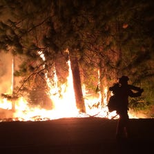 A firefighter walks past the King Fire on Highway 50 near Fresh Pond, Calif.