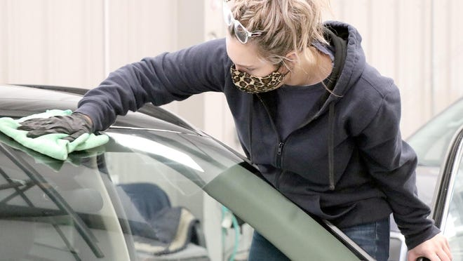Sydney Owens, a detailing specialist at Auto Park Ford in Sturgis, cleans a vehicle Monday at the dealership. The business is offering free detailing to qualifying health care workers and first-responders.