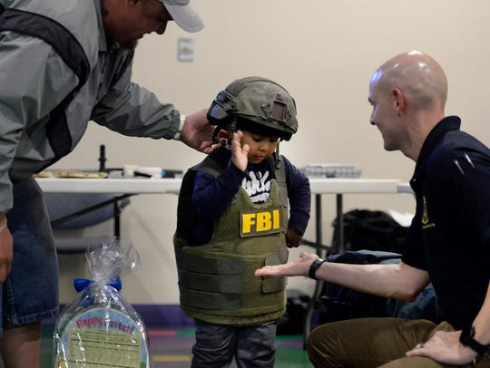 Raymond Sanchez, 3, slaps hands with Federal Bureau