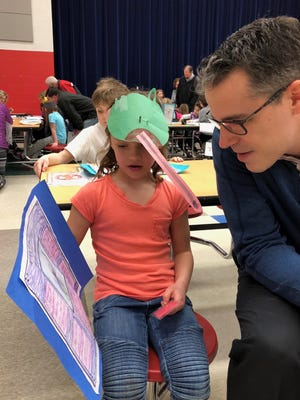 Josephine Pulis,7, shares her research about frogs with Harlan Principal Alex Agius. She told him about a frog called a glass frog.