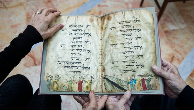 In this photo taken Wednesday, April 13, 2016, Eli and Shuli Barzilai holds a copy of the Birds' Head Haggadah in his house in Jerusalem. The Barzilai family grandchildren of one of the earliest Jewish victims of the Nazis are laying claim to a jewel of Israel's leading museum: the world's oldest surviving illustrated Passover manuscript.