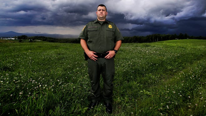 In this July 10, 2018 photo, with storm clouds on the horizon, U.S. Border Patrol Agent Richard Ross, the agent in charge of the area just below the Quebec border, poses for a portrait in a field where people entering the United States illegally from Canada have been apprehended, in Derby Line, Vt. While the Trump administration fortifies the southern border, there's growing concern over the number of foreigners entering the country illegally across the porous northern border with Canada. (AP Photo/Charles Krupa)