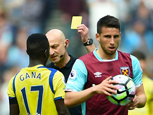 Everton's Idrissa Gueye is shown the yellow card by referee Roger East, during the English Premier League soccer match between West Ham United and Everton, at London Stadium, in London, Saturday April 22, 2017. (Daniel Hambury/PA via AP)