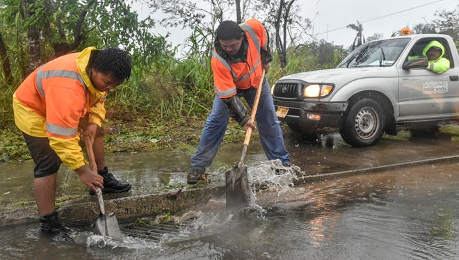 Jeremiah Santos, left, and Albert Moro of the Department of Public Works Highway Maintenance section, clear a storm drain to prevent flooding along Route 10 in Mangilao after Typhoon Dolphin on May 16.