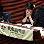 Pro-democracy lawmaker Claudia Mo reacts next to a crossed-out sign to symbolize her opposition to the election reform proposals during a legislature debate in Hong Kong Wednesday, June 17, 2015.