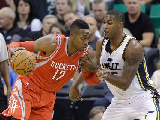 Houston Rockets' Dwight Howard (12) drives to the basket as Utah Jazz's Derrick Favors (15) defends in the first half of an NBA basketball game Wednesday, Oct. 29, 2014, in Salt Lake City. (AP Photo/Rick Bowmer)