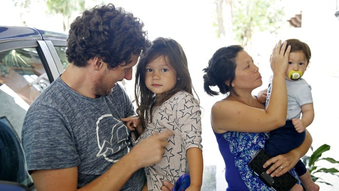 Marco Costella and his wife, Dina Habaue, try to entertain their children Maia, 3, and Mattia, 14 mo., while they wait for a room at the Travelodge on North Monroe Thursday after a long night of driving from Fort Lauderdale. The family plans to push on to Alabama, depending on the path the Hurricane Irma takes.