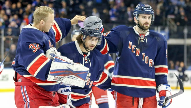 New York Rangers goalie Antti Raanta (32) and defenseman Keith Yandle (93) celebrate with right wing Mats Zuccarello, center, (36) after the game against the Toronto Maple Leafs at Madison Square Garden .