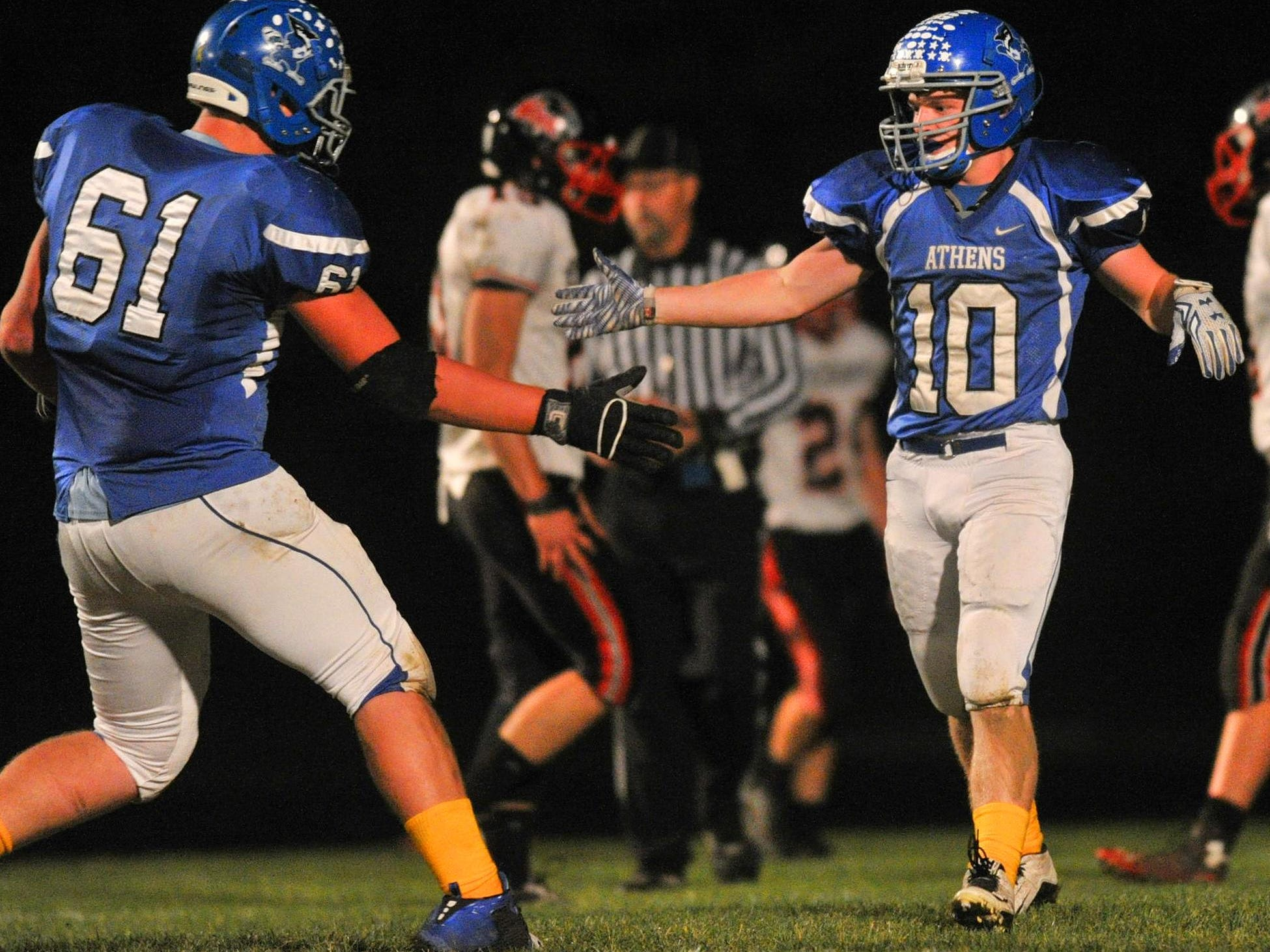 Athens' Jake Stange(10), right, receives a highfive for a run touchdown he made during Friday night's Cloverwood Conference boys football matchup between Owen-Withee and Athens at Athens High School football field