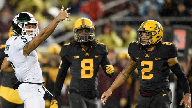 Hunter Rison #5 of the Michigan State Spartans celebrates a first down as Duke McGhee #8 and Jacob Huff #2 of the Minnesota Golden Gophers look on during the first quarter of the game on October 14, 2017 at TCF Bank Stadium in Minneapolis, Minnesota.