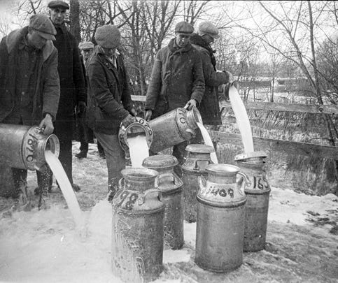 Picketers dumping milk from trucks who refused to turn back during the milk strikes of 1933. Customary procedure when a driver refused to follow orders.