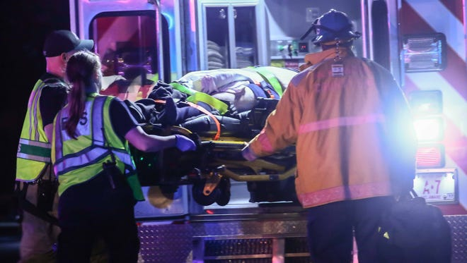 Paramedics help load a victim of a two-vehicle crash into an ambulance early Sunday morning.