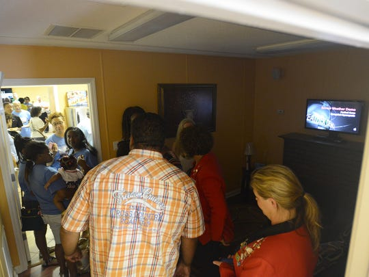 People are seen in the severe weather demonstration room while touring the Freeland Reaves Life Safety House on Friday, July 1, 2016.