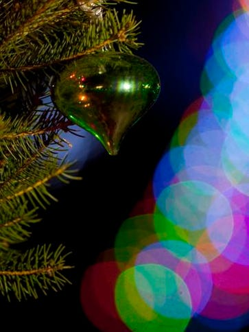 Christmas lights glow near a tree adorned with ornaments in Finley River Park in Ozark .