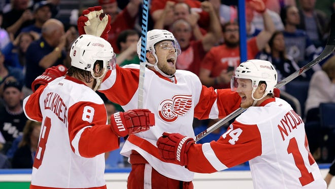Detroit Red Wings center Riley Sheahan, center, celebrates his goal against the Tampa Bay Lightning with Justin Abdelkader, left, and Gustav Nyquist, right, during the first period of Game 5 of a first-round NHL Stanley Cup hockey playoff series Saturday, April 25, 2015, in Tampa, Fla.