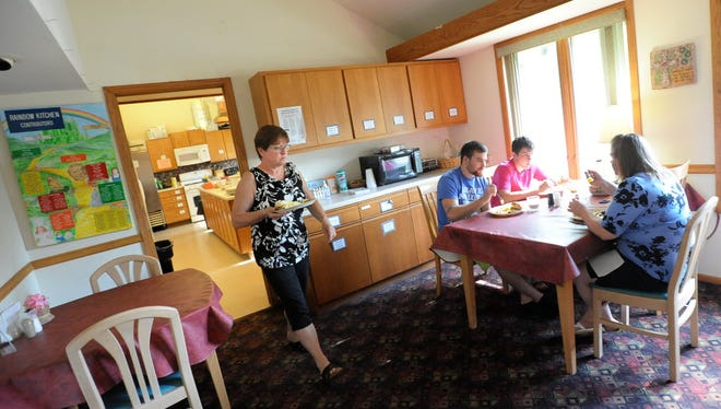 Deb Gallet of Gilman, Wis., gets some food with other guests at Kathy's House in 2015.