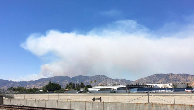 A fast-growing brush fire burns in Santa Clarita, Calif., Sunday, June 25, 2017. The fire sparked when a car crashed on a Los Angeles County freeway.
