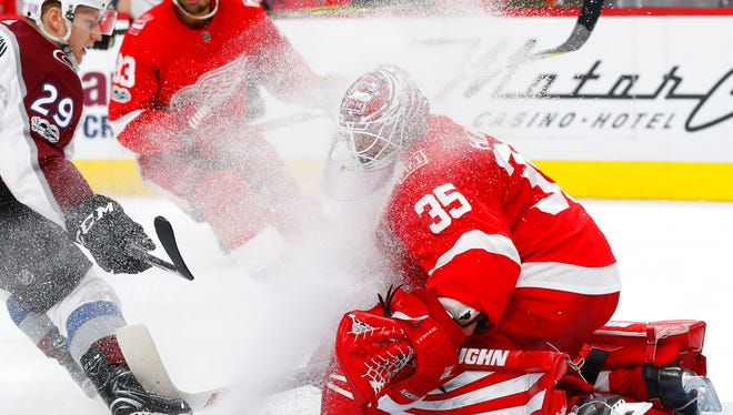 Colorado Avalanche center Nathan MacKinnon (29) sprays Detroit Red Wings goalie Jimmy Howard (35) with ice while having his shot blocked in the second period.