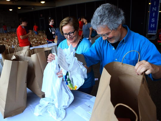John Otto (right) and Becky Johnson check their Beach 2 Bay packet during the Beach 2 Bay packet pickup Friday, May 19, 2017, at the Congressman Solomon P. Ortiz Center in Corpus Christi.