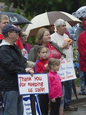 People watch and bring signs with messages to the Memorial Day procession on May 25, 2015.