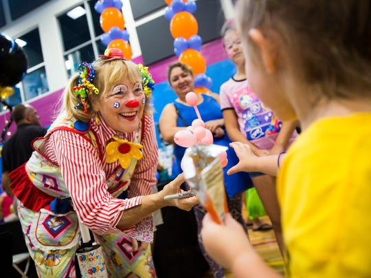 Melody Merrymaker hands a balloon poodle to Grace Cosslett, 3, during the Back to School Expo on Saturday, August 12, 2017 at the Greater Naples YMCA in North Naples. The event featured more than 55 vendors, offering information on goods and services families need for the school year.