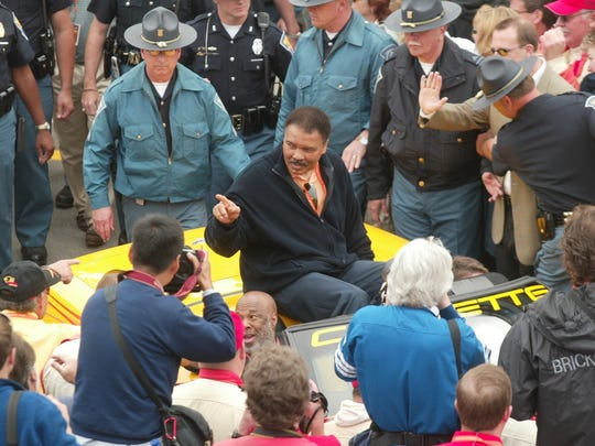 Muhammad Ali is surrounded by fans, photographers and police officers at the 2003 edition of the Indianapolis 500.