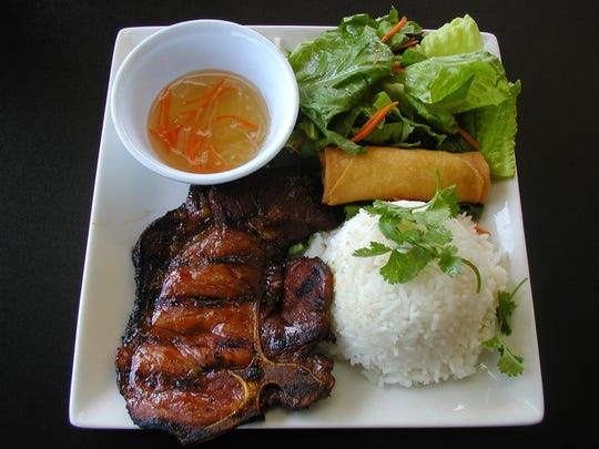 This house special includes grilled pork chop, rice, egg roll, salad and dressing on the side.