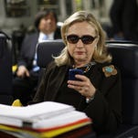 FILE - In this Oct. 18, 2011, file photo, then-Secretary of State Hillary Rodham Clinton checks her Blackberry from a desk inside a C-17 military plane upon her departure from Malta, in the Mediterranean Sea, bound for Tripoli, Libya. (AP Photo/Kevin Lamarque)