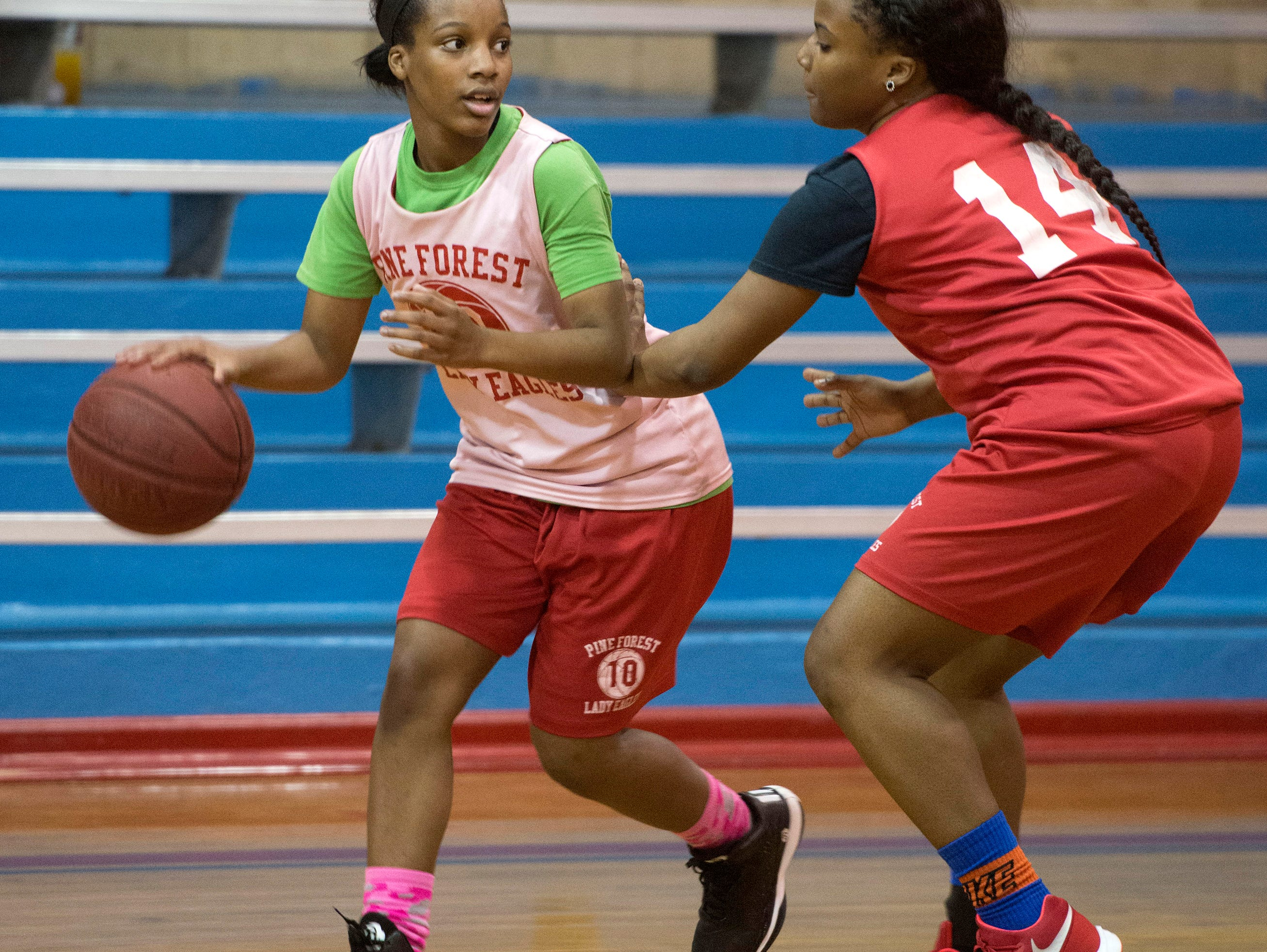 Kendauria Brooks, (No. 10) left, and Quiyana Riley, (No. 14) right, work through drills during practice as The Pine Forest High School girls basketball team prepare for an upcoming district 1-6A tournament.