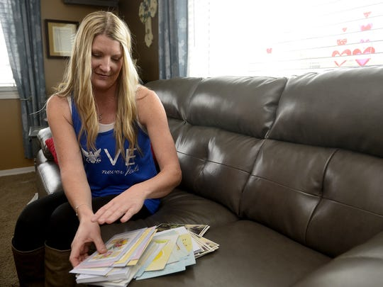 Robynn Dunn, who lost her husband Deputy Joe Dunn in August 2014, shows a stack of thank-you cards she is working on to thank people for the love and support her family received after her husband's death.