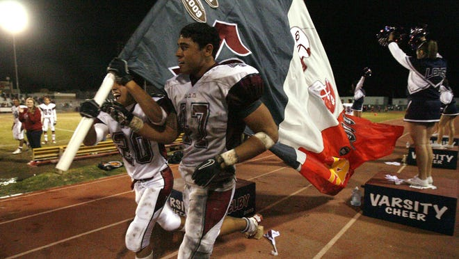 Manny Saenz (left) and Nuuvali Faapito of La Quinta High School football carry the Victory Flag after their team defeated Palm Desert High School 28-13 November 12, 2010. Wade Byars, The Desert Sun
