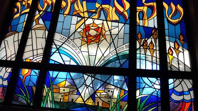 The stained glass window of Temple Emanu-El tells the story of Passover. The temple is among the houses of worship that have canceled services for the time being.