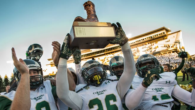 C.J. Leonard (8), Kevin Pierre-Louis (26) and their CSU teammates celebrate with the Bronze Boot after beating Wyoming in the 2015 Border War game in Laramie. Wyo.