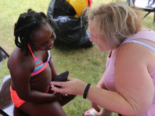 Zechia Mickler (left), of Beacon, looks at a photo of the painted flower on her cheek on Claudia Heckert's (right) phone. She has Down syndrome, and her mother, Donalee Mickler, took her to Red Wing Park in East Fishkill on Sunday for its inclusive A Day at the Beach event.