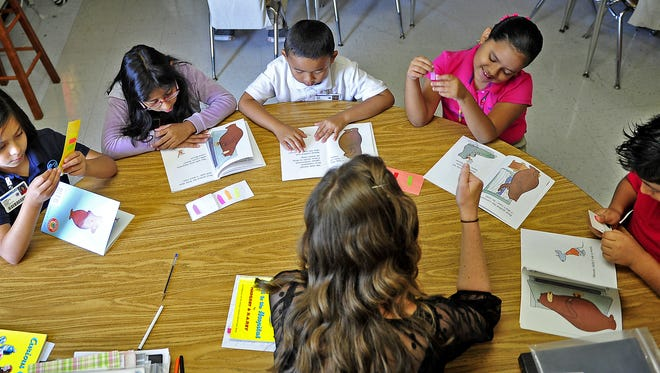 Third-graders, from left, Karen Zavaleta, Genesis Maranda, Puoe Aung, Jakeline Cruz and Axel Barrera take part in a reading session in Brittney Hannah's class for English-language learners at Cole Elementary School.