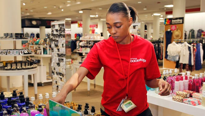 Aziana Johnson, a Backstage sales clerk, straightens items in the Fresh Scent area as the Macy's department gets ready to open in 2017.