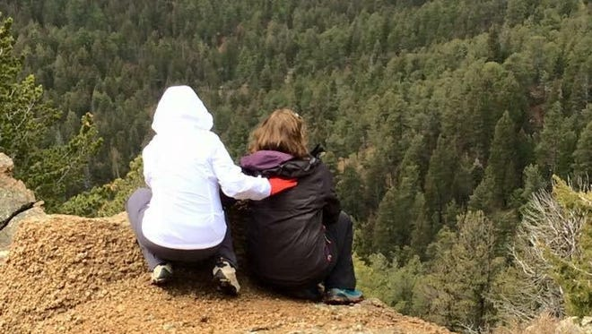 Laura Varon Brown, right, sits with Kathy Barry, Steve Anderson's sister, at the spot where they left his ashes last month near Gray Back Peak in Colorado, the state where Anderson was born.