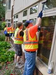 Career One summer camp participants including Dylan Turney, right, 16, wash windows on a crew Thursday, July 21, at St. Benedict's Senior Community. The Career One program introduces kids to careers and teaches them the basics about applying for jobs and adopting a good work ethic.